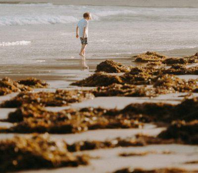 jongen loopt op strand